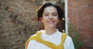 Zwolnione tempo portret zdejmuje okulary przeciwsłonecznych ono uśmiecha się outdoors nastoletni dzieciak zbiory