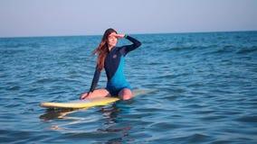 Zwolnione tempo: potomstwa schudnięcia kipieli dziewczyna patrzeje zmierzch Pławiki na kolorze żółtym wsiadają w otwartym morzu,  zbiory wideo