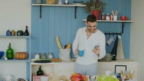 Zwolnione tempo Przystojny młody śmieszny mężczyzna taniec, śpiew w kuchni i podczas gdy surfujący ogólnospołecznych środki na je zbiory wideo