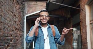 Zwolnione tempo radosny amerykanin afrykańskiego pochodzenia facet opowiada na telefonie komórkowym outdoors zdjęcie wideo