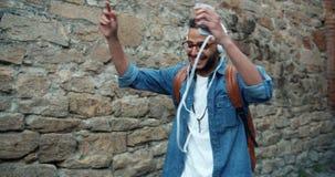 Zwolnione tempo radosny amerykanin afrykańskiego pochodzenia facet słucha muzyka w hełmofonach zbiory wideo