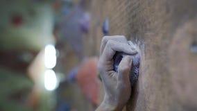 Zwolnione tempo rockowego arywisty ręka w kredzie, chwyty pięcie kamień podczas gdy trenujący w wspinaczkowym gym zdjęcie wideo
