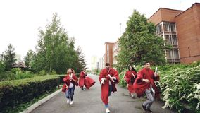 Zwolnione tempo rozochoceni przyjaciół ucznie biega na kampusie z dyplomami, rzucający mortarboard nakrętki, łapie one i zdjęcie wideo