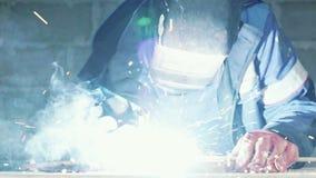 Zwolnione tempo, spawacz w spaw masce spawa dwa metal części Robociarz w coveralls pracuje indoors zbiory