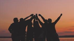 Zwolnione tempo sylwetki grupy tana otuch młodzi ludzie i przyjęcia przy plażą na zmierzchu zbiory wideo