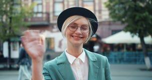 Zwolnione tempo szczęśliwa dziewczyny falowania ręka w ulicie patrzeje kamerę w mieście zdjęcie wideo