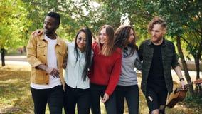 Zwolnione tempo szczęśliwi młodzi ludzie przyjaciół chodzi wpólnie w parku w jesieni mienia gitarze opowiada i śmia się młodość zbiory wideo