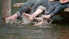Zwolnione tempo szczegół rodzinni cieki bawić się w wodzie podczas gdy relaksujący na drewnianym pontonie zbiory