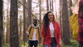 Zwolnione tempo uśmiechnięci młodzi ludzie chodzi w lasowym i patrzeje wokoło cieszyć się dalej piękną naturę i świeże powietrze zbiory