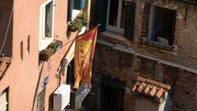 Zwolnione tempo venetian chorągwiany falowanie w wiatrze na flagpole przy Wenecja miastem