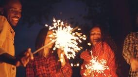Zwolnione tempo z podnieceniem młodzi ludzie najlepszych przyjaciół tanczy z Bengal światłami outdoors i śmia się mieć zabawę zdjęcie wideo