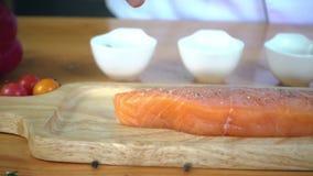 Zwolnione tempo - Zamyka up wyśmienity szef kuchni lub kucharz przyprawia świeżego kawał delikatesy kawałek łosoś ryba z morze so zbiory