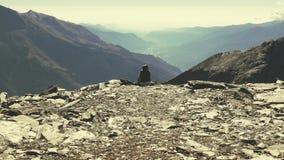 Zwolnione tempo zoom osamotniony kobiety obsiadanie na skalistym terenie i dopatrywaniu ekspansywny widok nad doliną zdjęcie wideo