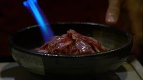 Zwolnionego Tempa cheff oparzenie azjatykci plasterek surowa wołowina z blowtorch w restauracji zbiory