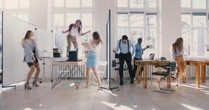 Zwolnionego tempa dolly strzał ludzie biznesu tanczy w lekkim nowożytnym biurowym przyjęciu, wieloetniczny drużynowy odświę zdjęcie wideo