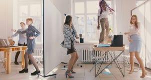 Zwolnionego tempa dolly strzał, szczęśliwi wieloetniczni koledzy tanczy na lekkim nowożytnym biurowego przyjęcia odświętno zbiory