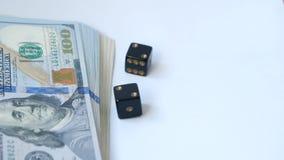 Zwolnionego tempa dwa czarne kostki do gry, bzdury, rzucać na białym tle, blisko paczki dolary, para dwa Poj?cie uprawia? hazard zbiory