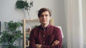 Zwolnionego tempa portraif stoi w domu z rękami krzyżować atrakcyjna osoba zdjęcie wideo