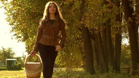 Zwolnionego tempa steadicam wideo piękna dziewczyna niesie kosz w brown kurtki odprowadzeniu przez jesień lasu zbiory