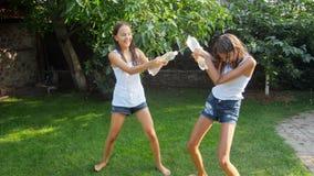 Zwolnionego tempa wideo dwa rozochoconej roześmianej dziewczyny bryzga wodę nad each inny od plastikowych butelek i nalewa zbiory