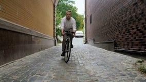 Zwolnionego tempa wideo eleganckiego czerwonego brodatego mężczyzna jazdy puszka stara wąska ulica na bicyklu zbiory