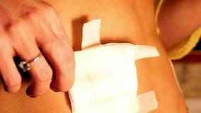 Zwolnionego tempa zbliżenia kobieta usuwa bandaż od przebijania zbiory