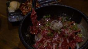 Zwolnionych Temp ludzie używa chopsticks dla jeść plasterek surowa wołowina z ryż zdjęcie wideo