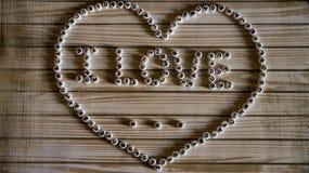 Zwrota ` kocham ` duży serce komponował biały, round, klingerytów bloki na drewnianej powierzchni Obraz Stock