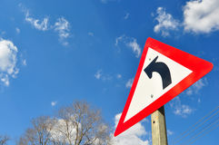 Zwrota ruchu drogowego znak przeciw niebieskiemu niebu z chmurami Zdjęcie Royalty Free
