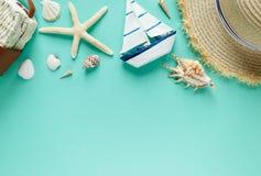Zwrotnika mieszkanie kłaść z słomianym kapeluszem, torba, rozgwiazda, skorupy, łódź, kolczyki na zielonym tle Lato mody mieszkani zdjęcie stock