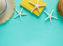 Zwrotnika mieszkanie kłaść z słomianym kapeluszem, torba, rozgwiazda, skorupy, żółty blanknote na pastel zieleni tle Lato kreatyw zdjęcia stock