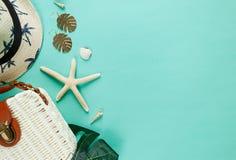 Zwrotnika mieszkanie kłaść z słomianym kapeluszem, torba, rozgwiazda, skorupy, okulary przeciwsłoneczni, łódź, kolczyki na zielon obrazy stock