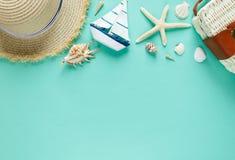 Zwrotnika mieszkanie kłaść z słomianym kapeluszem, torba, rozgwiazda, skorupy, okulary przeciwsłoneczni, łódź, kolczyki na zielon obraz stock