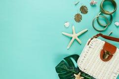 Zwrotnika mieszkanie kłaść z słomianym kapeluszem, torba, rozgwiazda, skorupy, okulary przeciwsłoneczni, łódź, kolczyki na zielon obrazy royalty free