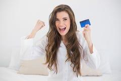 Zwycięska przypadkowa brown z włosami kobieta trzyma kredytową kartę w białych piżamach Obraz Royalty Free