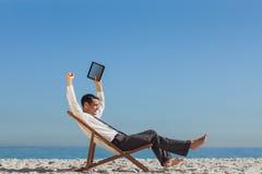 Zwycięski młody biznesmen odpoczywa na jego pokładu krześle trzyma h Obrazy Stock