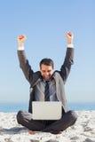 Zwycięski młody biznesmen patrzeje jego laptop Zdjęcia Stock