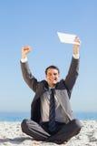 Zwycięski młody biznesmen trzyma up jego pastylkę komputerowa Obrazy Royalty Free