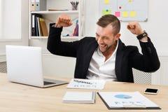 Zwycięzca, pomyślny biznesmen przy miejscem pracy obraz stock