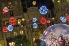 Zwyczajna ulica iluminująca Bożenarodzeniową dekoracją z dużą szklaną piłką w przedpolu Zdjęcie Stock