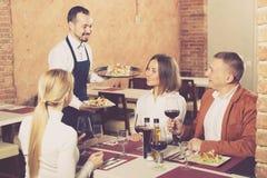 Zwyczajny męski kelnera przewożenia rozkaz dla gości Fotografia Stock