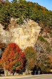 Zwykły rockowy blef w jesieni z pinen drzewa r na wierzchołku i drzewa z barwionym ulistnieniem, dwa pasów ruchu autostradą i skr zdjęcie stock