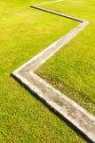 Zygzakowaty Betonowy krawężnik i Zielona trawa Obraz Stock