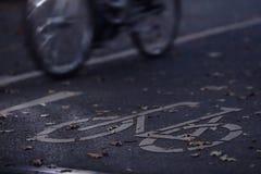 Zyklusweg in der Dämmerung des frühen Morgens mit Fahrrad und in differntiated Beleuchtung im Hintergrund - städtisches austausch stockfotografie