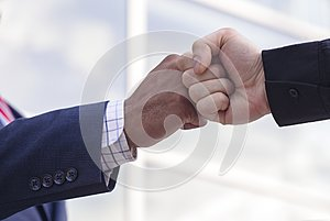 Close-up of two businessmen giving fist bump