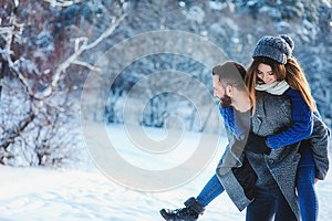 Happy loving couple walking in snowy winter forest, spending christmas vacation together. Outdoor seasonal activities