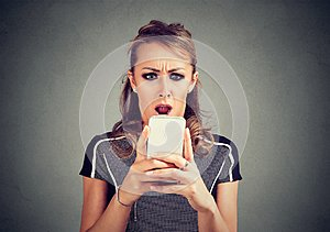 Funny shocked scared woman looking at phone seeing bad news photos message with disgusting emotion on face
