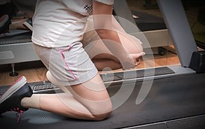 Asian woman runner got sports injury on machine treadmill at fitness gym