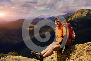 Young male hiker with backpack relaxing on top of a mountain during calm summer sunset