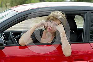 Female rookie new driver young beautiful woman scared and stressed while driving car in fear and shock